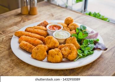 Vegetable veg tempura platter  -  vegetarian dish - deep fried sweet potato, mushrooms, cauliflower, served with homemade chilli and mayonnaise dips . Served with fresh salad leaves. Restaurant style.