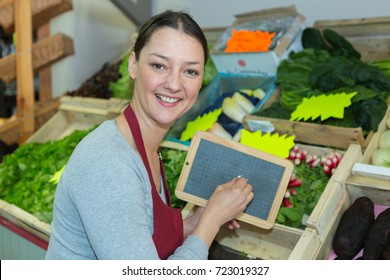 vegetable vendor holding a small chalkboard