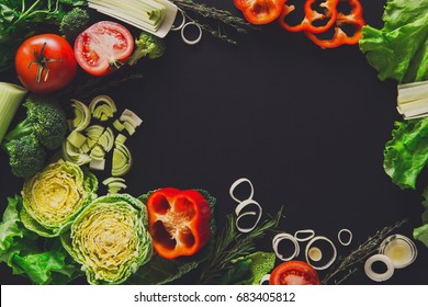 Vegetables background. Fresh organic food, peppers, leek and greens on black. Natural food with copy space.