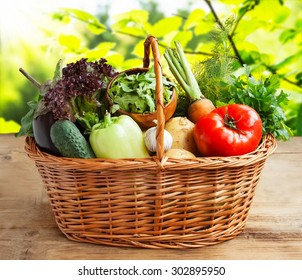 Vegetables Basket with Tomato, Arugula, Salad,Eggplant,Potatoes,Carrots, Garlic and Greens on Wooden Board in Nature