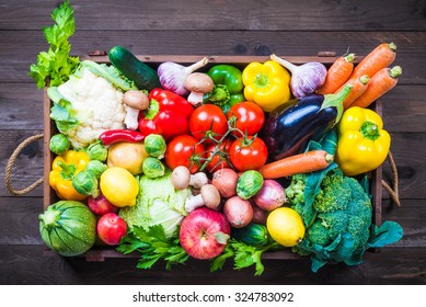 Vegetables in box on dark background, delivery organic food concept.