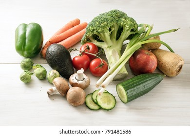 vegetables, broccoli, carrots, peppers, parsnip roots, mushrooms, tomatoes, green onions, avocado, brussels sprouts from above on a white wooden background, healthy food and slimming low carb diet