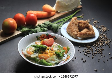 vegetables clear soup,with brocoli  fresh tomato carot and cabbage served with fried meatball tofu