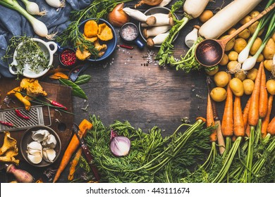 Vegetables cooking ingredients for tasty vegetarian dishes. Carrot , potato , onion , mushrooms , garlic , thyme , parsley on dark rustic wooden background, frame