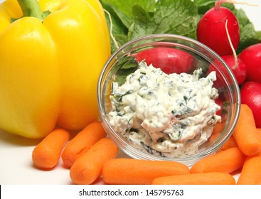 Vegetables and Dip Spinach dip in a round clear bowl, surrounded by fresh vegetables.  The vegetables are yellow pepper, carrots and radishes.