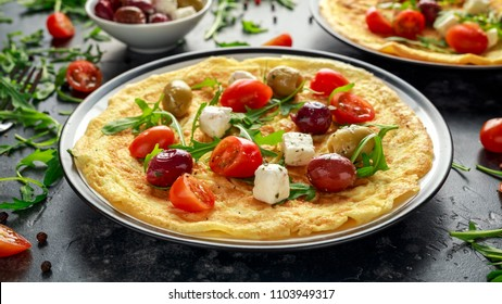 Vegetables Eggs Omelette with tomatoes, wild rocket, greek cheese, olives in a plate. Morning breakfast. healthy food