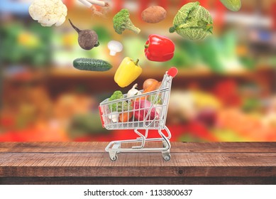 Vegetables fall in market cart on wooden table.  Market with fresh vegetables in background.