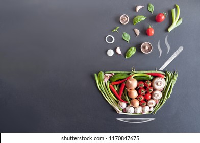 Vegetables falling into a bowl shape on a chalkboard with sketch of steam, spoon and saucer