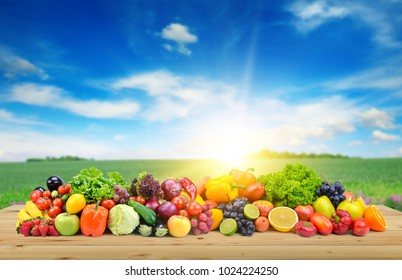 Vegetables and fruit on wooden table of boards against background of spring field and bright blue sky.