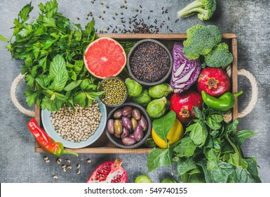 Vegetables, fruit, seeds, cereals, beans, spices, superfoods, herbs, condiment in wooden box for vegan, gluten free, allergy-friendly, clean eating and raw diet. Grey concrete background and top view