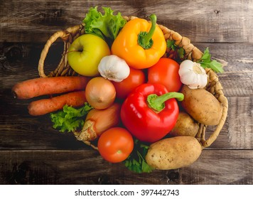 Vegetables and fruits in a basket on wooden background