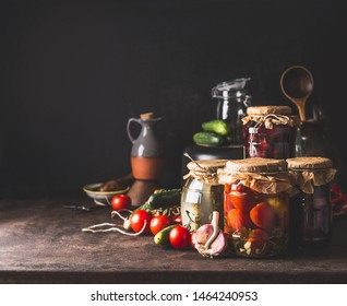 Vegetables and fruits canning. Various preserve glass jars on dark table. Homemade harvest storage. Copy space. Healthy food.