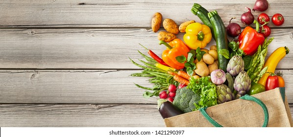 Vegetables and fruits falling out of tipped over bag next to large empty space over rustic wooden background
