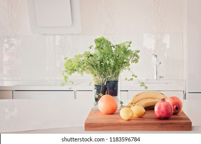 Vegetables and fruits on a clean table, granate apple, lemons, grape fruit, bananas, all white kitchen interior with herbs, coriander, parsley, salad with Scandinavian style