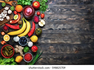 Vegetables and fruits on a dark rustic wooden table. Healthy vegetarian food.