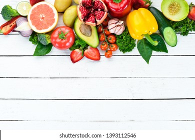 Vegetables and fruits on a white wooden background. Melon, strawberries, potatoes, kiwi fruit, pomegranate, citrus, avocados. Top view. Free space for your text.