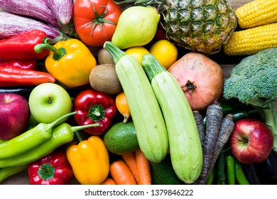 Vegetables and fruits on the wooden background. Organic foods and fresh vegetables. Cucumber, cabbage, pepper, salad, carrot, broccoli, lemon, lettuce and tomato on the table.
