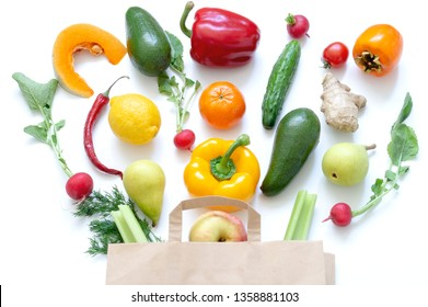 Vegetables and fruits in paper bag on white background. Mango, radish, yellow pepper, red pepper, lemon, cucumber, dill, tangerine, parsley.