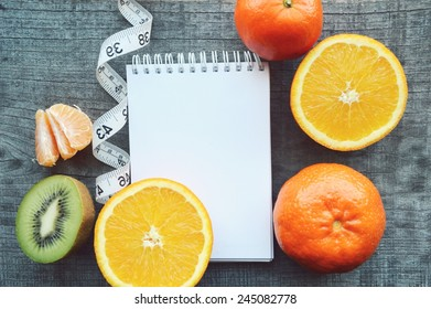 vegetables and fruits for weight loss, a measuring tape, diet, weight loss,notebook, diary, orange, tangerine, banana, kiwi