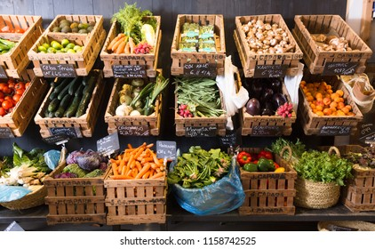 vegetables and fruits in wicker baskets on counter of greengrocery. on labels of product names in Catalan