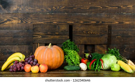 Vegetables from garden or farm close up. Homegrown vegetables. Fresh organic vegetables on dark wooden background. Grocery shop concept. Autumn harvest organic crops pumpkin corn vegetables.