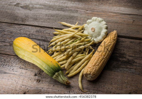 vegetables  green beans, corn, zucchini, squash on old wooden background in rustic style