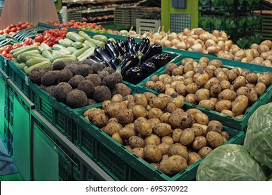 Vegetables in green plastic crates, supermarket food store, toned