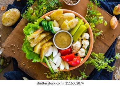 Vegetables healthy buddha bowl in clay bowl.  Tomatoes, cucumbers, cauliflower, backed potato, eggplant, dip sauce. Ideal dietary lunch, dinner. Raw vegan vegetarian healthy food