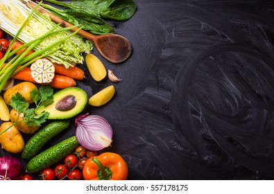 Vegetables, herbs, raw ingredients for cooking and wooden spoon on rustic black chalk board background. Healthy, clean eating concept. Vegan or gluten free diet. Space for text. Top view. Salad making