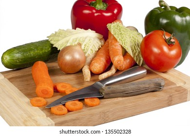 Vegetables and knifes on cutting board isolated on white background