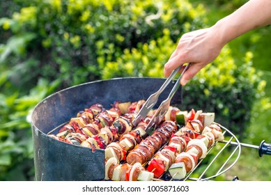 Vegetables and meat kebabs grilled over the coals on barbecue grill, people grilling food outdoors
