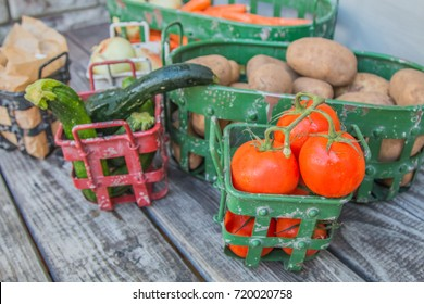 Vegetables in metal baskets on distressed vintage wood background