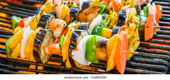 Vegetables mix cooked spicy skewers kebab on the BBQ. Background grill grid with fire flames