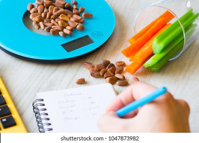 Vegetables and nuts on the scales. Calorie counting.