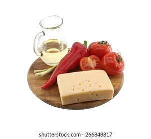 Vegetables, oil and cheese on cutting board, isolated on white background