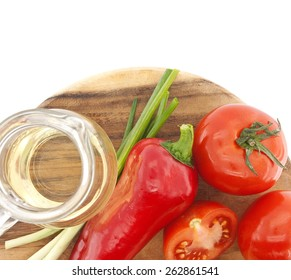 Vegetables and oil on cutting board, isolated on white background. Top view.
