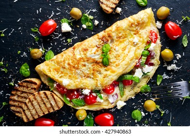 Vegetables Omelette with tomatoes, basil, greek cheese, parmesan, olives, toast.