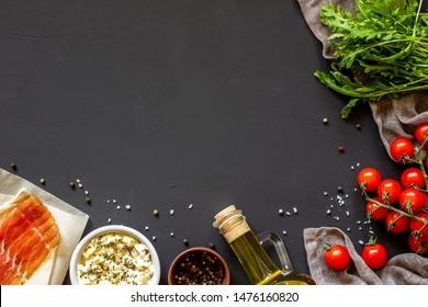Vegetables on a dark background. Italian cuisine. Tomatoes, arugula bacon