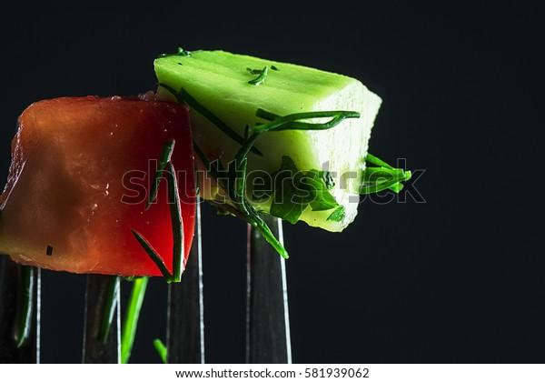 Vegetables on a fork, close-up. Dark background. Focus on vegetables