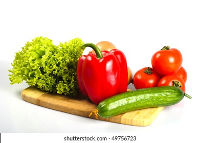 Vegetables on hardboard in kitchen for salad, isolated on white