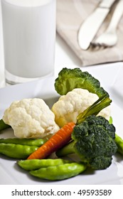 Vegetables On Plate With Glass Of Milk And Cutlery