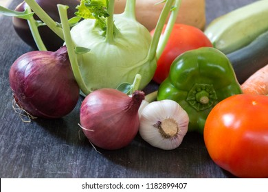 Vegetables on the table: red onion, garlic, kohlrabi cabbage, green bell pepper, tomato, zucchini