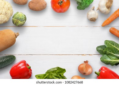 Vegetables on white wooden desk. Space for text in the middle.