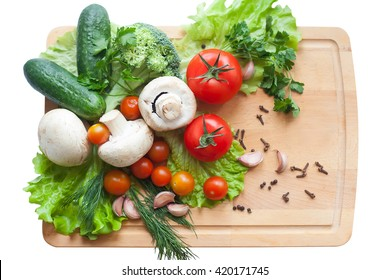 Vegetables on wood background, mushrooms, cucumbers, tomatoes, broccoli, lettuce, dill, parsley and pepper on isolated white background