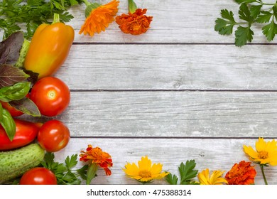 Vegetables, parsley and basil, flowers on wooden background.