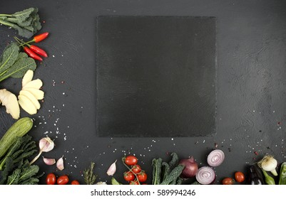 vegetables and plate on a black background