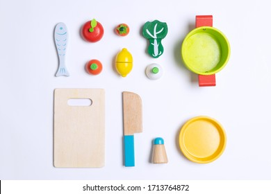 Vegetables, pot, fish and kitchen utensils toys made from wooden for kids to play on top of white background