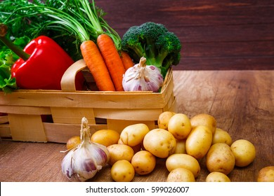 Vegetables. Potatoes, carrot and red pepper. Lettuce salad, garlic and brocoli. Wooden basket on rustic table.