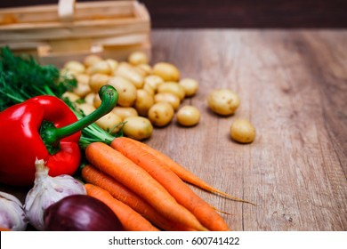 Vegetables. Potatoes, carrot and red pepper. Garlic and onion. Natural organic bio food. Wooden basket on rustic table.