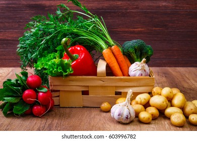 Vegetables. Potatoes, carrot and red pepper. Lettuce salad, garlic and brocoli. Red radish. Wooden basket on rustic table.